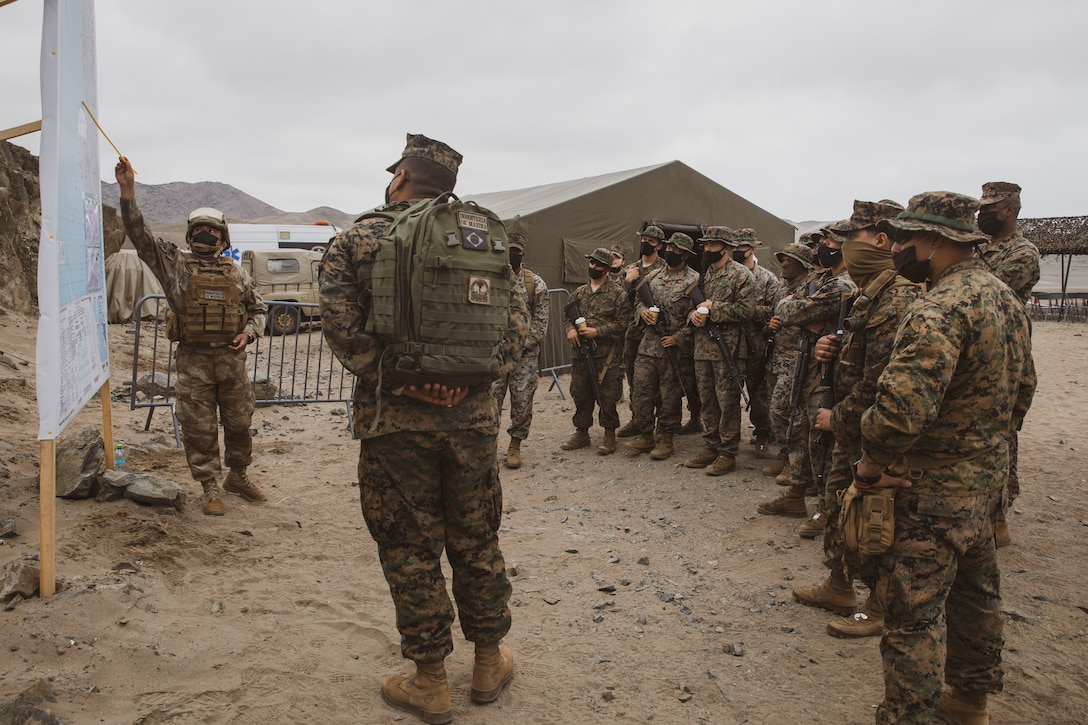 U.S. Marines with Special Purpose Marine Air-Ground Task Force - UNITAS get briefed on the events of an amphibious landing during UNITAS LXII in Salinas, Peru, Oct. 2, 2021. UNITAS is the world's longest-running maritime exercise. Hosted this year by Peru, it brings together multinational forces from twenty countries and includes 29 ships, four submarines, and twenty aircraft conducting operations off the coast of Lima and in the jungles of Iquitos. The exercise trains forces to conduct joint maritime operations and focuses on strengthening partnerships and increasing interoperability and capability between participating naval and marine forces.