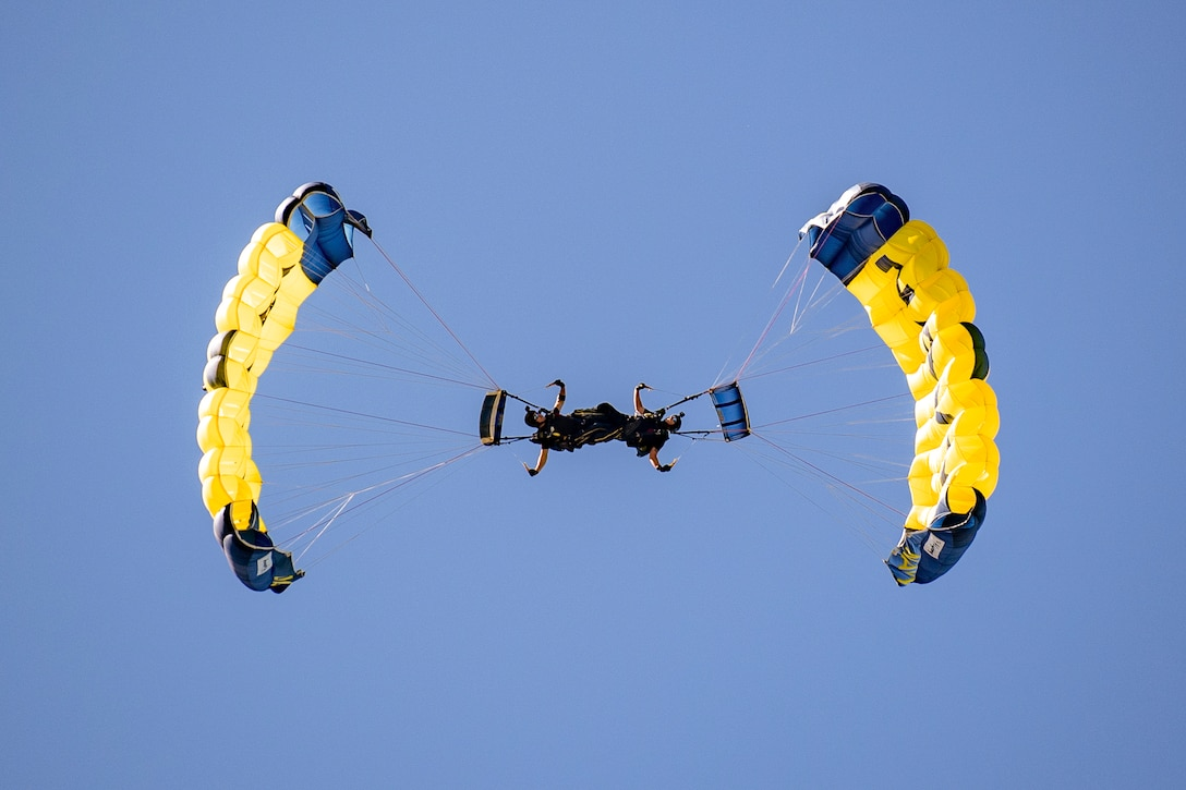 Two sailors perform with parachutes in the air.