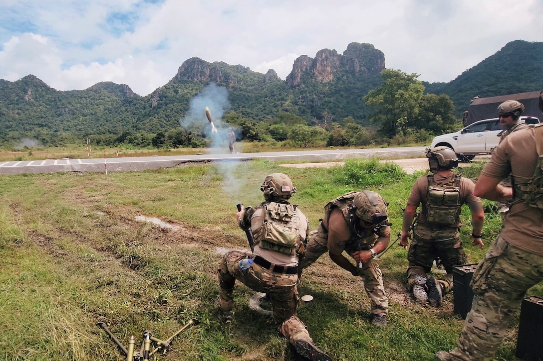 Soldiers fire a weapon in a field towards mountains.
