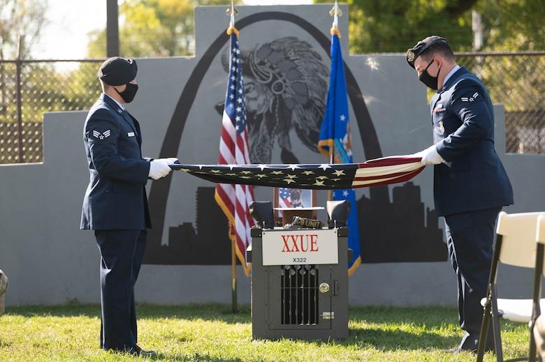 Honor Guard members fold a U.S. flag at a military working dog memorial.