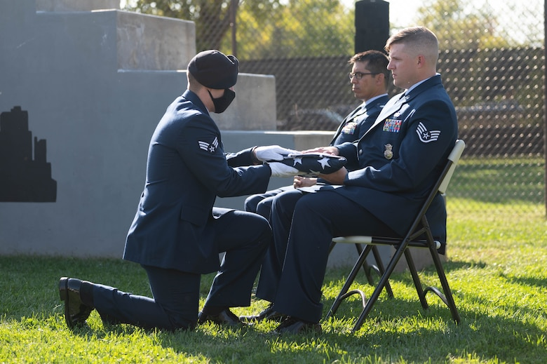 Honor Guard member hands a U.S. flag to the handler of deceased military working dog at a memorial.