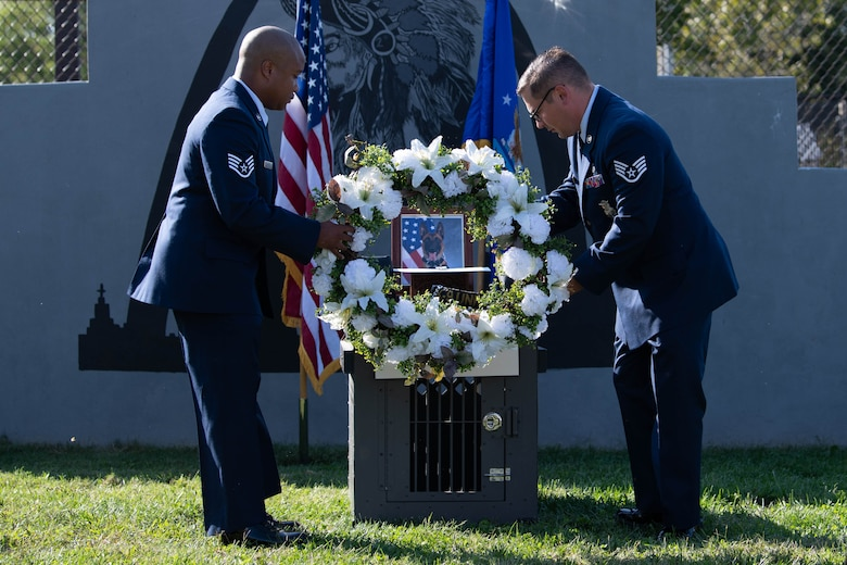 Two Airmen lay a wreath upon the memorial of a military working dog.