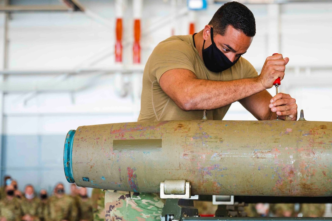 An airman secures a munition to an aircraft.