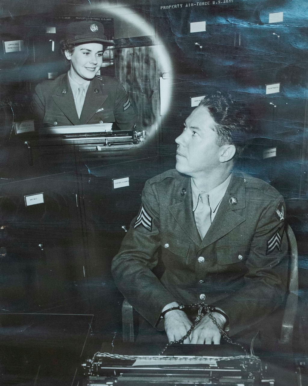 A World War II-era black-and-white recruitment photo shows a man at a typewriter looking up at a woman seated in front of a typewriter.