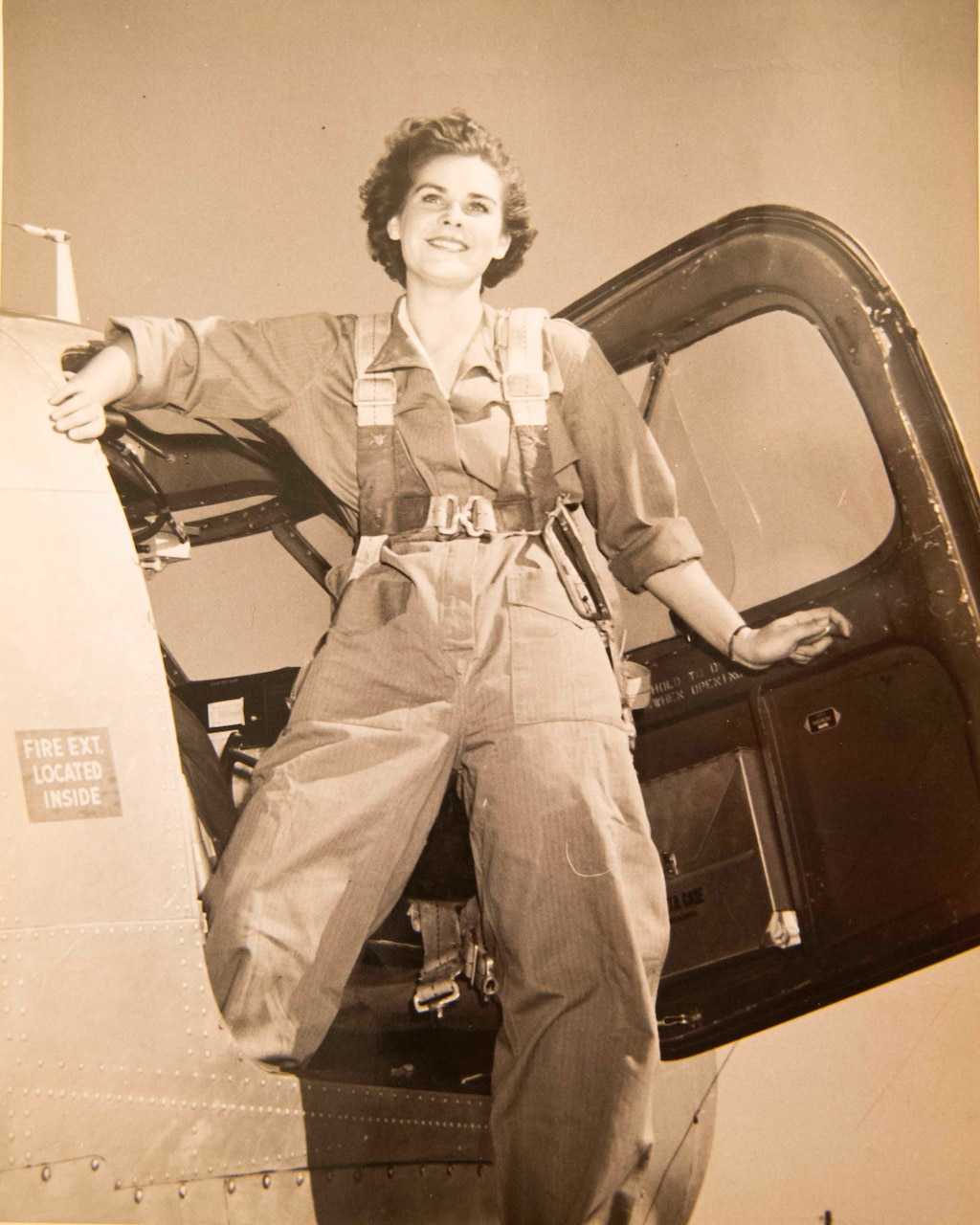 A World War II-era photo shows a woman in a flight suit stepping out of a military aircraft.