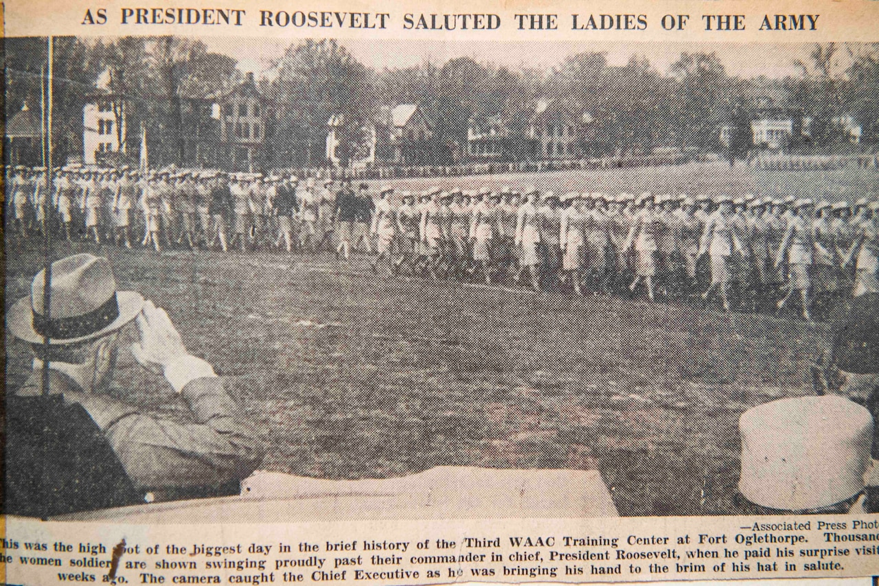 An old newspaper clipping of a man saluting women in military uniform is shown.