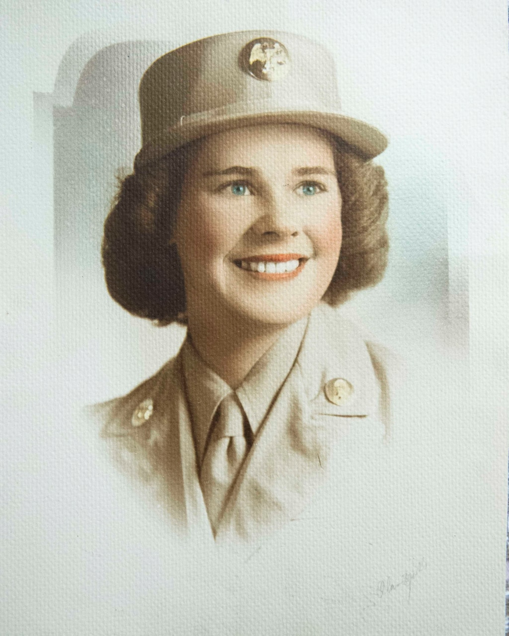 A woman military uniform poses for a photo.