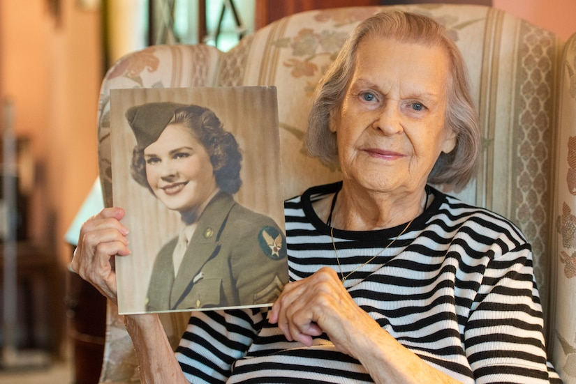 A woman holds an old photo of a woman in military uniform.