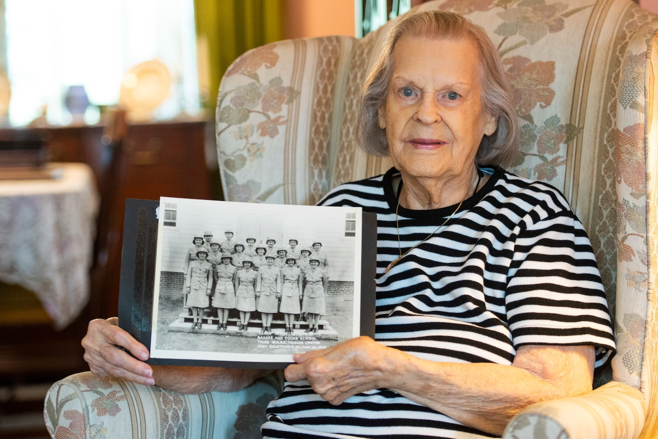 A  woman holds a black-and-white photo of women in military uniform.