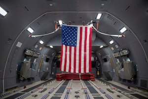 A flag is hung in the back of a KC-46 Pegasus at Altus Air Force Base, Oklahoma, Oct. 8, 2021. This flag was flown inside the aircraft for the funeral of U.S. Army Air Forces 2nd Lt. Ernest Vienneau, former 97th Bombardment Group pilot, to be later given to Veinneau's family. (U.S. Air Force photo by Staff Sgt. Cody Dowell)