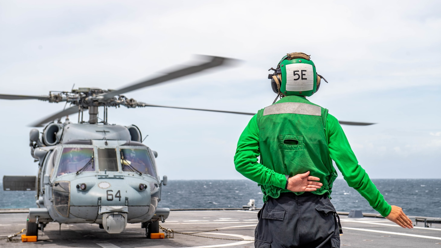 A Sailor signals to a MH-60S Sea Hawk Helicopter aboard the Independence-variant littoral combat ship USS Charleston (LCS 18), during flight operations.