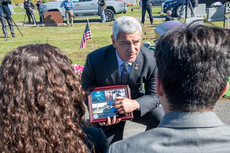 Kelly McKeague, Defense POW/MIA Accounting Agency (DPAA) director, presents a plaque from his agency to the family of U.S. Army Air Forces 2nd Lt. Ernest Vienneau, former 97th Bombardment Group pilot, during Vienneau's funeral at Millinocket, Maine, Oct. 9, 2021. The DPAA vision is to provide a world-class workforce that fulfills the nation's obligation by maximizing the number of missing personnel accounted for while ensuring timely, accurate information is provided to their families. (U.S. Air Force photo by Staff Sgt. Cody Dowell)