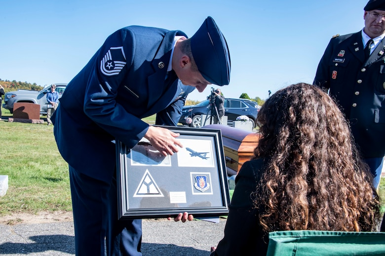 U.S. Air Force Master Sgt. Brad Edwards, 58th Airlift Squadron loadmaster, presents a plaque from the 97th Air Mobility Wing (AMW) to the family of U.S. Army Air Forces 2nd Lt. Ernest Vienneau, former 97th Bombardment Group pilot, during Vienneau's funeral at Millinocket, Maine, Oct. 9, 2021. The plaque showcased the aircraft that Vienneau flew and the aircraft that was flown over the funeral by members of the 97th AMW. (U.S. Air Force photo by Staff Sgt. Cody Dowell)