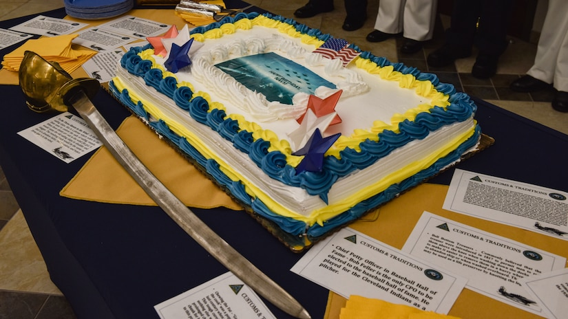 Sailors and Joint partners gathered at the Lakehurst Flight Deck Community Center to celebrate the U.S. Navy's 246th birthday at Joint Base McGuire-Dix-Lakehurst, N.J., Oct. 13, 2021. The ceremonial cake was surrounded by cards displaying facts about the Navy that those in attendance could read before the cutting. (U.S. Air Force Photo by Staff Sergeant Shay Stuart)