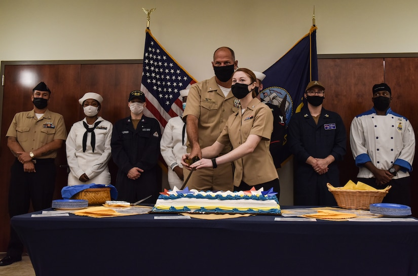 The most senior and junior Sailor in attendance cut the cake together during a ceremony celebrating the U.S. Navy's 246th birthday at Joint Base McGuire-Dix-Lakehurst, N.J., Oct. 13, 2021. The senior and junior Sailor cutting the cake is a tradition that symbolizes experienced Sailors leading younger Sailors that will become the future of the Navy. (U.S. Air Force photo by Staff Sergeant Shay Stuart)