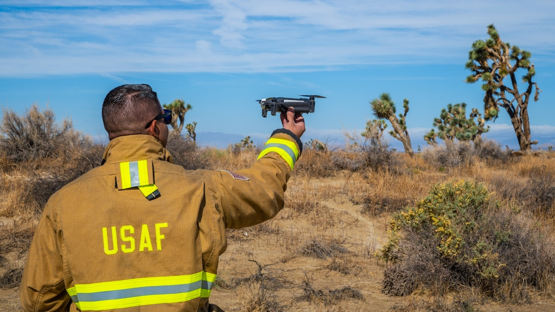 """Firefighter Harmon Deal, launches a drone during a """"Broken Arrow"""" training exercise on Edwards Air Force Base, California, Sept. 28. Edwards Fire and Emergency Services utilized the drone to better survey the incident area and provide vital information such as fires, casualties and other hazards to the incident commander. (Air Force photo by Katherine Franco)"""