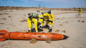 """Airmen from the Explosive Ordnance Disposal Flight, 812th Civil Engineer Squadron, gather radiation level readings from a simulated nuclear device during a """"Broken Arrow"""" training exercise on Edwards Air Force Base, California, Sept. 28. (Air Force photo by Katherine Franco)"""