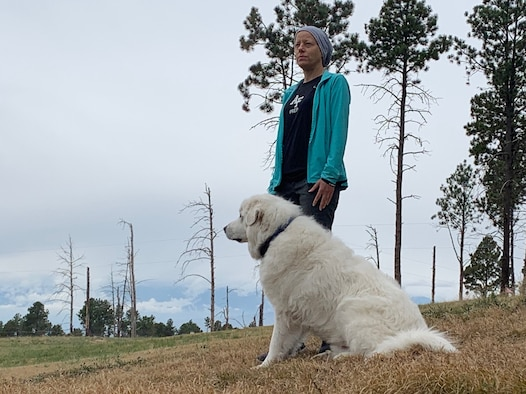 Image of a women standing with a dog.