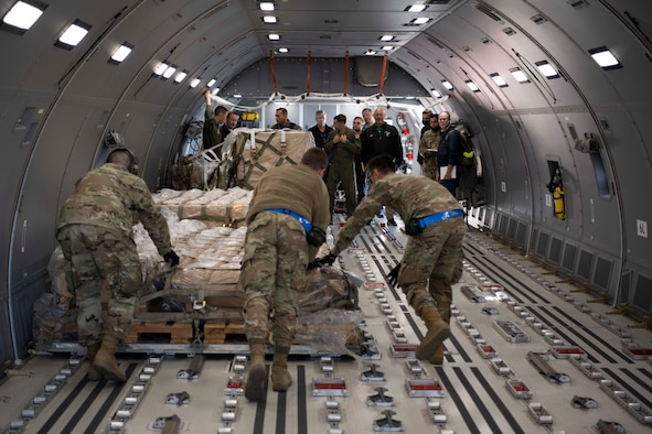 people spectate Airmen push cargo in an aircraft