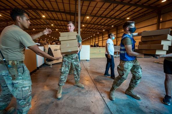Airmen work together to unload food for Afghanistan evacuees, Aug. 23, 2021, at Al Udeid Air Base, Qatar.