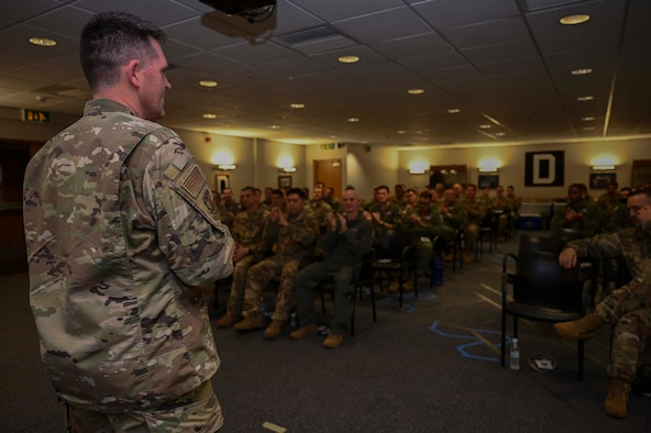 """U.S. Air Force Col. David Hood, 100th Maintenance Group commander, gives closing remarks at the 100th MXG dedicated flying crew chief ceremony at Royal Air Force Mildenhall, Oct. 7, 2021. Hood thanked distinguished Airmen for keeping adversaries at bay, noting the crew chiefs """"Carry the weight of the wing on their shoulders."""" (U.S. Air Force photo by Airman 1st Class Viviam Chiu)."""