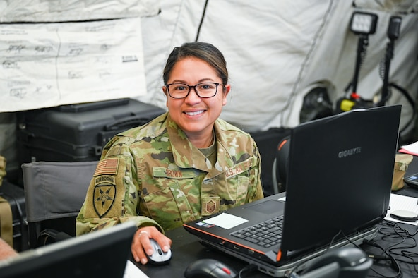 U.S. Air Force Master Sgt. Catherine Brown, 224th Joint Communications Support Squadron unit training manager, poses for a photo in her workspace during the Patriot North 2021 exercise located at Volk Field Air National Guard Base in Wisconsin June 15, 2021. Brown said she likes training opportunities like PATRIOT 21 because it gives her the opportunity to mobilize for annual training with the rest of the squadron and track the unit's training accomplishments on-site in real-time, which is something she doesn't often get the opportunity to do. (U.S. Air National Guard photo by Tech. Sgt. Caila Arahood)