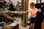 A military member hands a face mask to a child with outstretched arms as they are being carried by an adult woman.