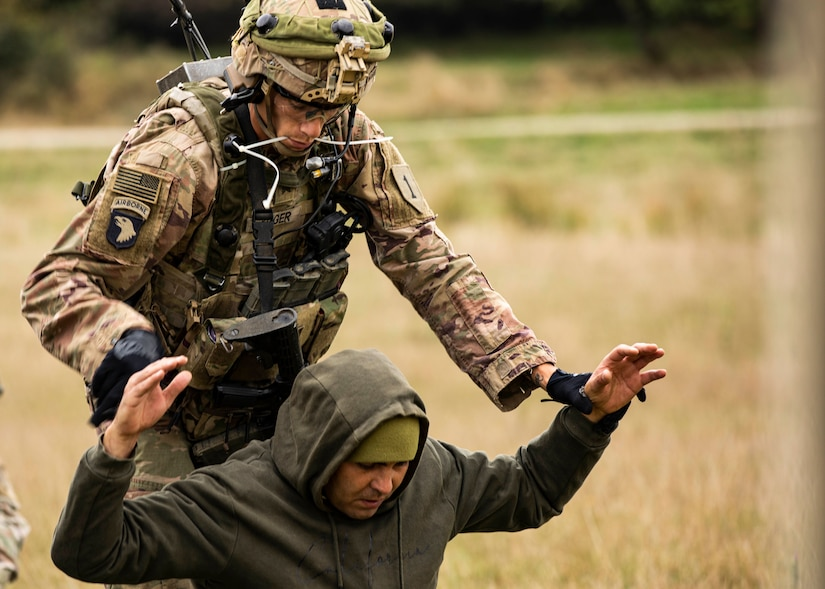 """U.S. Army Sgt. Benjamin Koger, Alpha Company, 1st Battalion, 16th Infantry Regiment """"Iron Rangers,"""" 1st Armored Brigade Combat Team, 1st Infantry Division, detains a prisoner of war during a multinational situational training exercise in Cincu, Romania"""