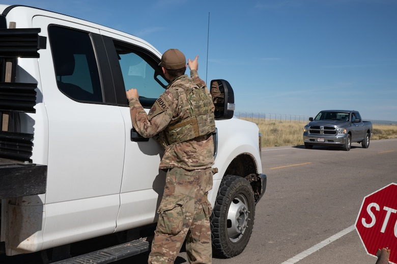 An Airman deployed with the 822nd Base Defense Squadron from Moody Air Force Base, Georgia, directs traffic down the road from Aman Omid Village on Holloman Air Force Base, New Mexico, Oct. 7, 2021. The Department of Defense, through the U.S. Northern Command, and in support of the Department of State and Department of Homeland Security, is providing transportation, temporary housing, medical screening, and general support for at least 50,000 Afghan evacuees at suitable facilities, in permanent or temporary structures, as quickly as possible. This initiative provides Afghan evacuees essential support at secure locations outside Afghanistan. (U.S. Army photo by Spc. Nicholas Goodman)