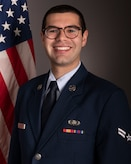 Official photo of A1C Cooper Johnson, horn with Heritage Winds and the Concert Band, two of six ensembles in the Air Force Heritage of America Band, Langley AFB, VA.  A1C Johnson is wearing blue service dress in front of an American flag.