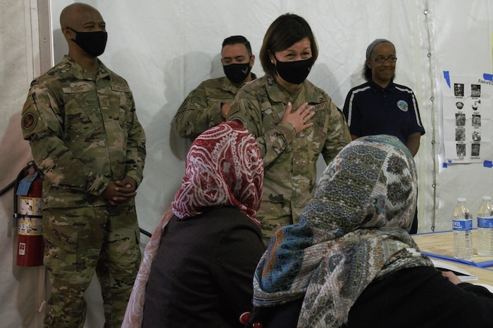 Chief Master Sgt. of the Air Force JoAnne S. Bass greets Afghan students during their English lessons at Aman Omid Village as part of a visit to Task Force-Holloman on Holloman Air Force Base, New Mexico, Oct. 13, 2021. The Department of Defense, through U.S. Northern Command, and in support of the Department of State and Department of Homeland Security, is providing transportation, temporary housing, medical screening, and general support for at least 50,000 Afghan evacuees at suitable facilities, in permanent or temporary structures, as quickly as possible. This initiative provides Afghan evacuees essential support at secure locations outside Afghanistan. (U.S. Navy photo by Mass Communications Specialist 1st Class Sarah Rolin)