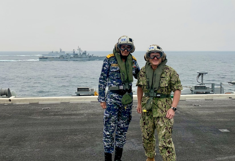 Two men in military uniforms stand on the flight deck of an aircraft carrier.