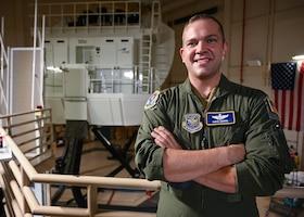 An Airman stands in front of a C-130J Super Hercules simulator.