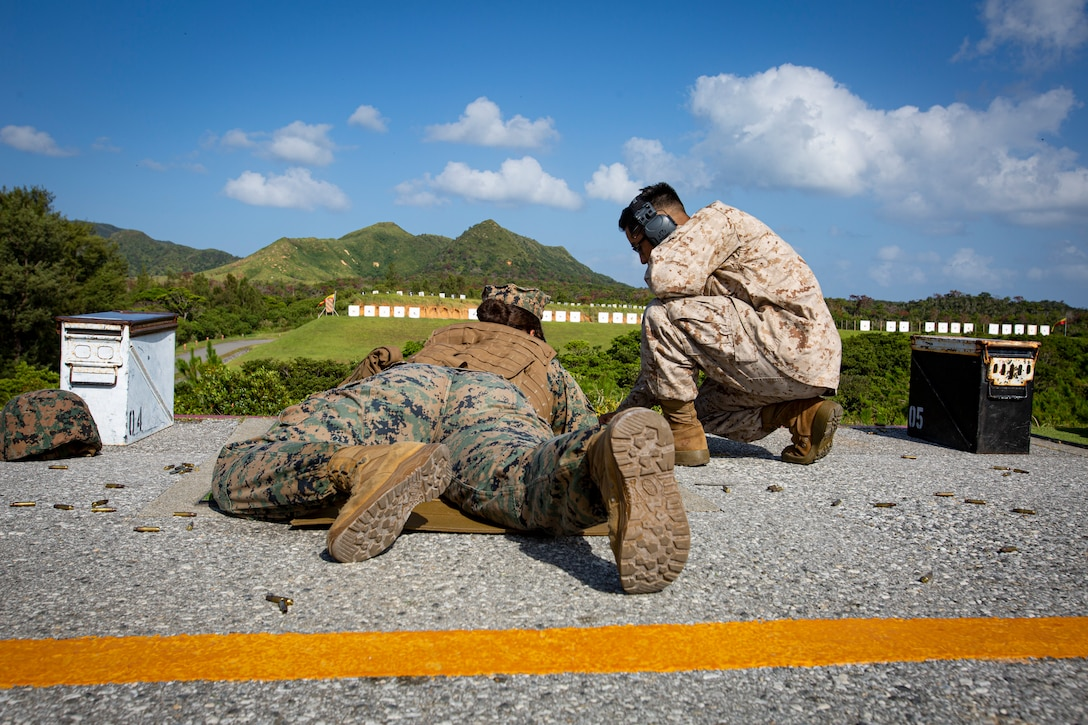 U.S. Marine Corps Sgt. Morelia Capuchino Diaz, a food service specialist with Camp Courtney Mess Hall, Combat Logistics Regiment 37, receives guidance from a Combat Marksmanship Coach during the new Annual Rifle Qualification on Camp Hansen, Okinawa, Japan, Oct. 5, 2021. The ARQ is a three-day, combat-centric course of fire that tests Marines' marksmanship skills in a dynamic-shooting environment. Shooters utilize artificial support, engage moving targets as well as engage targets while on the move.