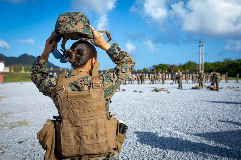 U.S. Marine Corps Sgt. Morelia Capuchino Diaz, a food service specialist with Camp Courtney Mess Hall, Combat Logistics Regiment 37, places on a kevlar as she walks to the firing line during the new Annual Rifle Qualification on Camp Hansen, Okinawa, Japan, Oct. 5, 2021. The ARQ is a three-day, combat-centric course of fire that tests Marines' marksmanship skills in a dynamic-shooting environment. Shooters utilize artificial support, engage moving targets as well as engage targets while on the move.