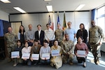 U.S. Army Garrison Japan Commander Col. Christopher Tomlinson, left, and USAG Japan Command Sgt. Maj. Justin Turner, right, pose for a group photo with members of the Air Force's 374th Contracting Squadron team Oct. 14 at Yokota Air Base, Japan, following an award ceremony where USAG Japan recognized the 374th CONS for their support with a USAG Japan budgetary mission.