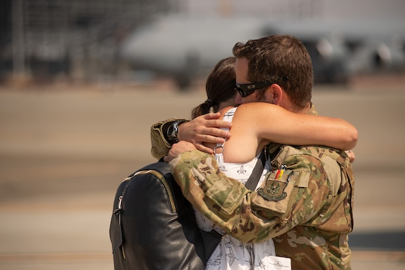 Maj. Dominic Calderon, a pilot from the 301st Airlift Squadron, embraces his wife upon arrival at Travis Air Force Base, California, September 14, 2021. Calderon's C-17 Globemaster III aircrew helped evacuate hundreds of American citizens, Special Immigrant Visa applicants and vulnerable Afghans from Afghanistan in support of Operation Allies Welcome