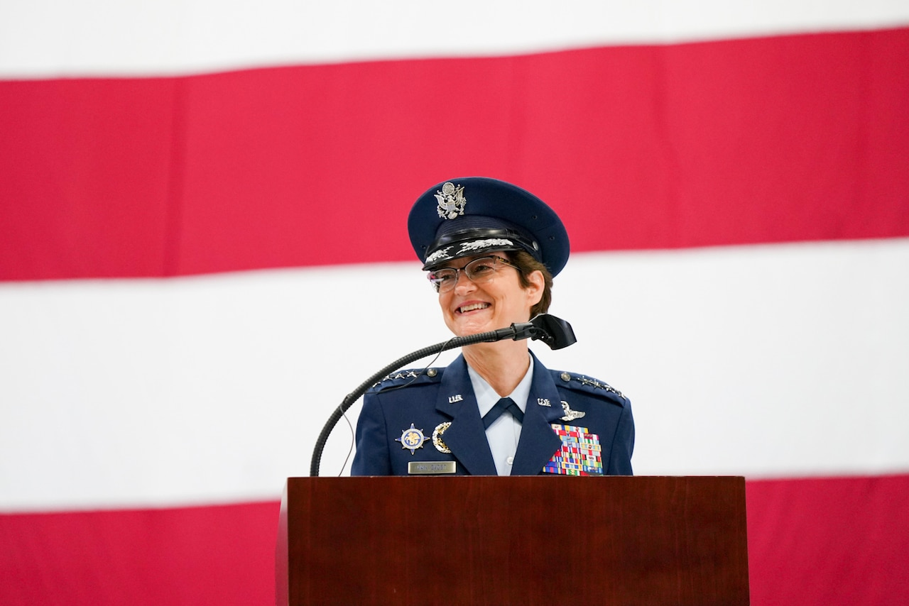 An Air Force general speaks at a lectern in front of a large American flag.