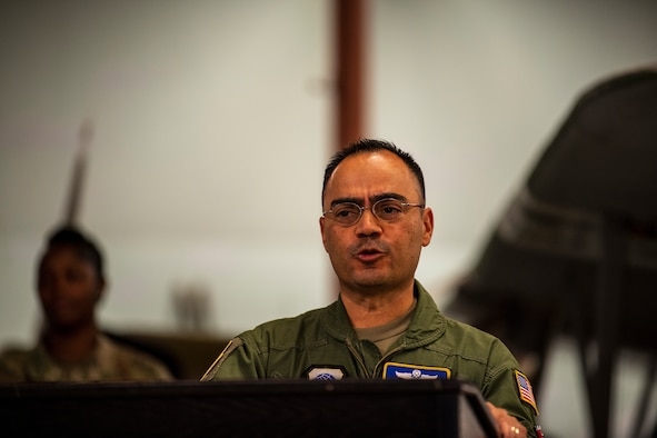 A man in a green uniform speaks from behind a podium.