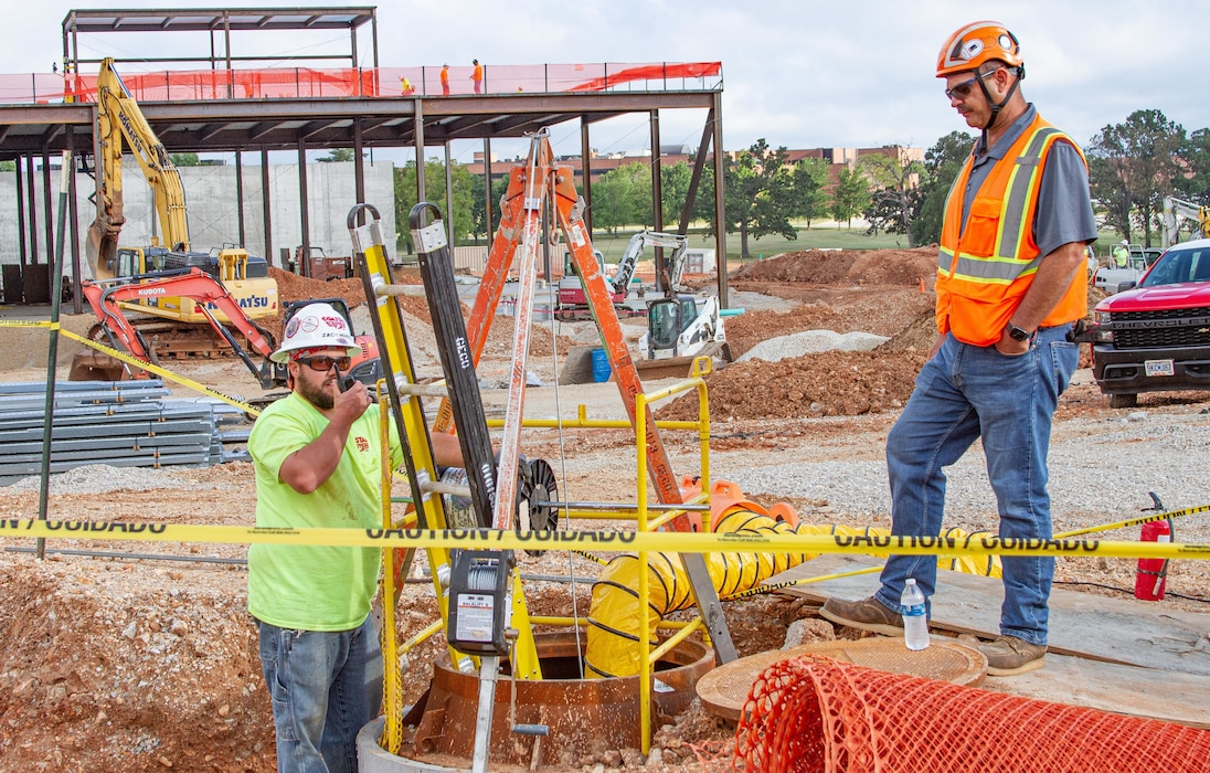 U.S. Army Corps of Engineers, Kansas City District Missouri Resident Office Hospital Low Voltage Quality Assurance Officer Ryan Snyder (right) works alongside the contracted low voltage quality control officer as he lowers wire underground on-site of the new hospital at Fort Leonard Wood, Mo., on Sept. 1, 2021.