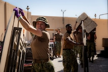 Sailors assigned to U.S. Naval Forces Central Command and Coastguardsmen assigned to Patrol Forces Southwest Asia participate in a community relations (COMREL) event at Bahrain Mobility International (BMI) in Isa Town, Oct 16. During the COMREL, more than 80 participants from multiple commands volunteered to assist with cleanup efforts, beautification projects and interactive programs with children.
