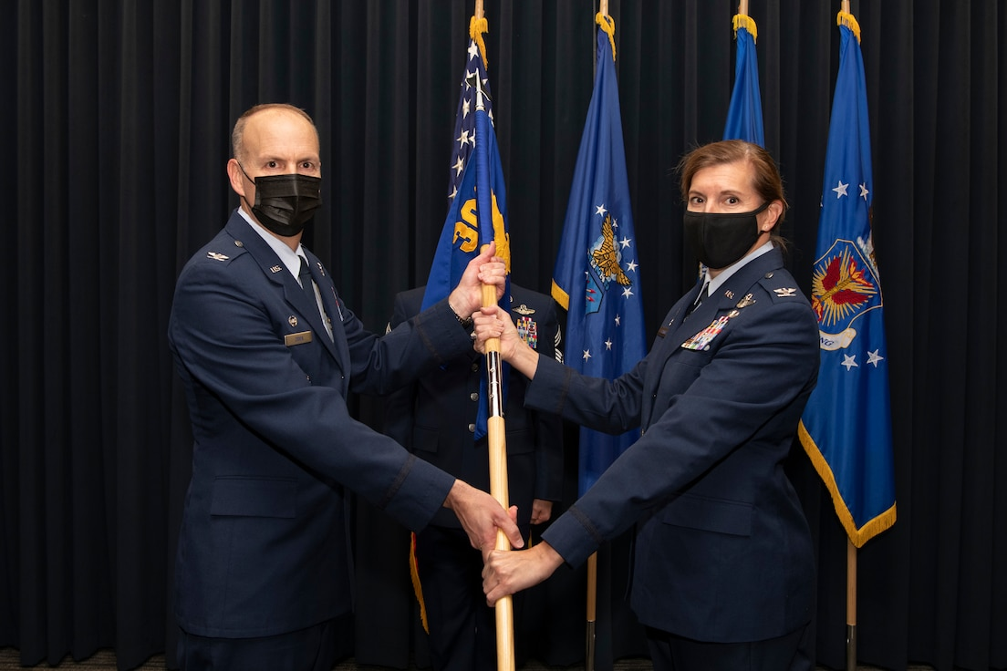 A man in Air Force service dress wearing a mask hands a blue flag attached to a wooden pole to a woman in Air Force service dress wearing a mask in front of four flags in the background.