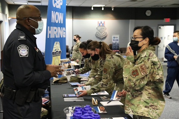 Female Airmen talk to Customs and Border Protection recruiter at a booth.
