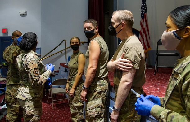 Airmen roll up sleeves before medical technicians.