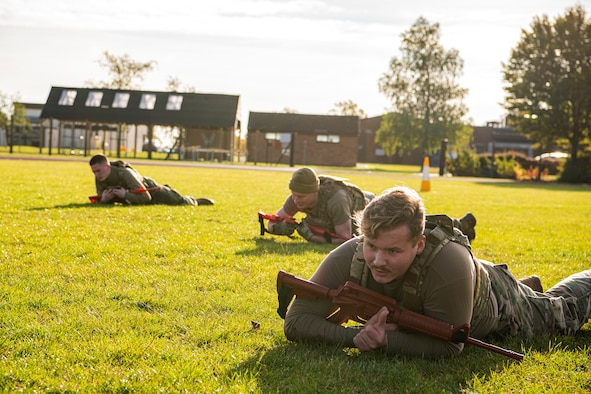 Airmen from the 423rd Security Forces Squadron, low crawl as part of a defender challenge at RAF Alconbury, England, Oct. 13, 2021. The challenge was part of National Police Week where defenders paid homage to those who have served as police officers and to honor those that lost their lives in the line of duty. (U.S. Air Force photo by Senior Airman Eugene Oliver)