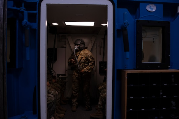 an airman stands in the hypobaric chamber instructing students on how to react to a rapid decompression