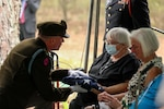 Col. Wes Morrison, commander of the North Carolina National Guard's 30th Armored Brigade Combat Team, presents folded flags to the family of 1st Lt. James E. Wright during a graveside service in his honor at the Oakdale Cemetery in Lumber Bridge, North Carolina, Oct. 12, 2021. Wright, who served with the NCNG's 120th Infantry Regiment, was killed in action near Dornot, France Sept. 10, 1944, and missing until his remains were recently identified.