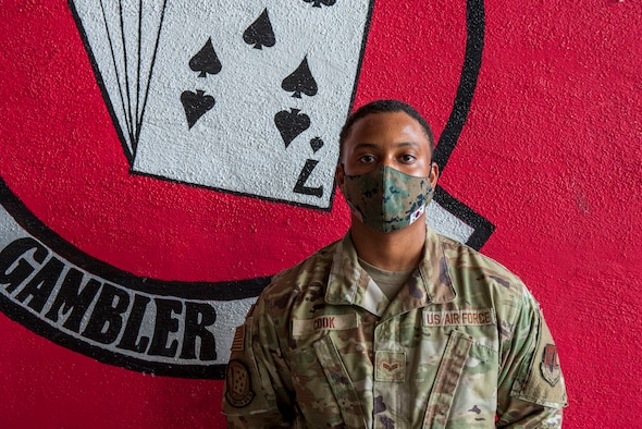 Photo of Airman in front of unit logo.