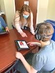 A teacher assists a student using a touchscreen device.