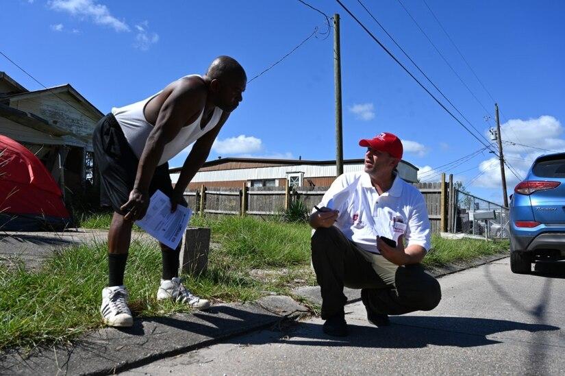 Two men speak on a street.